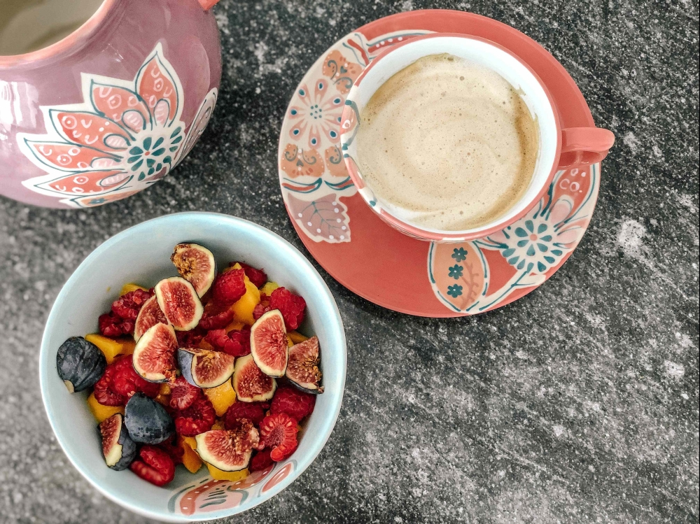 coffee with a fruit salad bowl